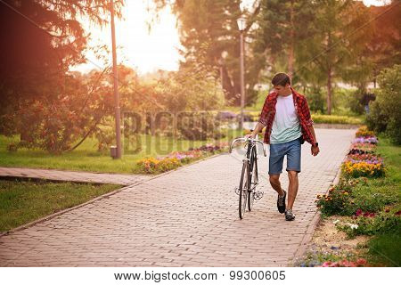 Hipster man with bicycle walking in the park