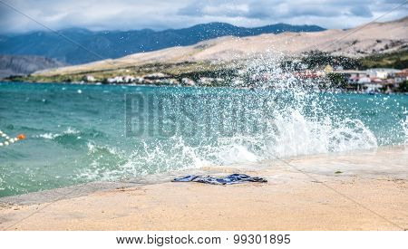 Wet Towel Laying On A Pier With Waves Splashing