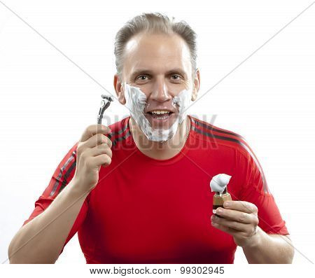 The sports man has a shave- with the razor and a small brush