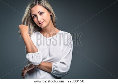 Portrait of a very attractive blonde, young woman on grey background, touching her lovely hair, looking both relaxed and confident (color toned image)