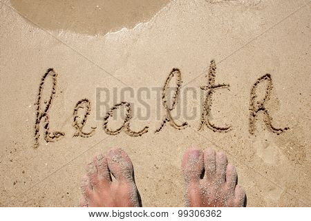 Conceptual health text hand written in sand on a beach on an exotic island background with feet