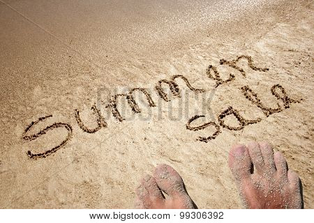 Conceptual Summer sale text hand written in sand on a beach on an exotic island background with feet