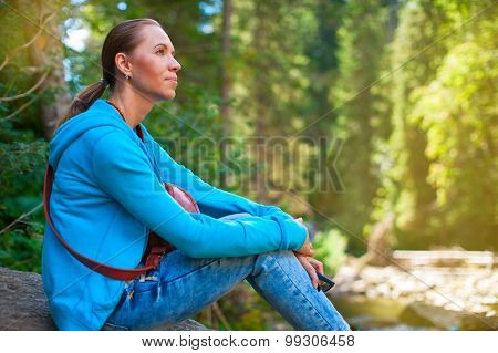 Portrait of attractive woman sitting in forest