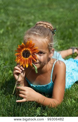 Little girl with a flower in summer time