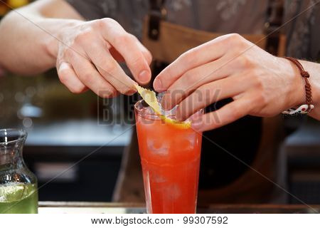 Bartender is adding lemon zest to the cocktail at bar counter