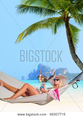 Young beautiful woman relaxing on the hammock under the coconut trees on the beach