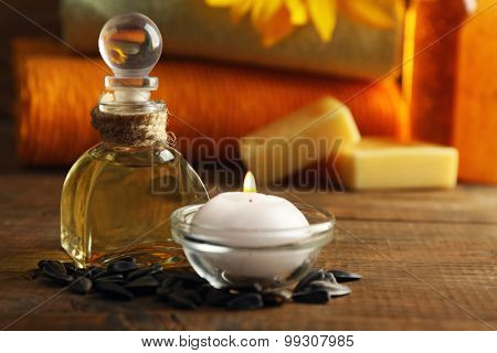 Massage oil and spa treatments, sunflower on wooden background