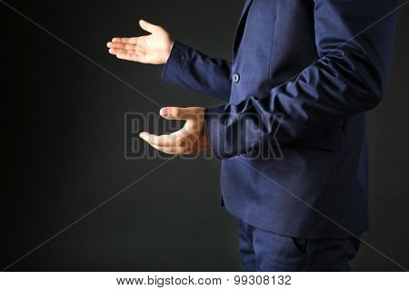 Businessman in suit introduce something on dark background