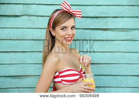 Beautiful girl with pretty smile  with cocktail on color wooden background