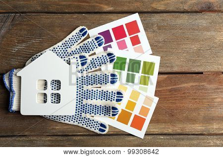Color samples, gloves and decorative house on wooden table background
