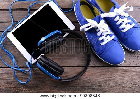 Headphones with sneakers and tablet on wooden background