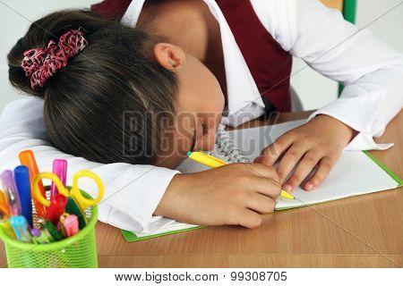 Beautiful little schoolgirl sleeping on desk