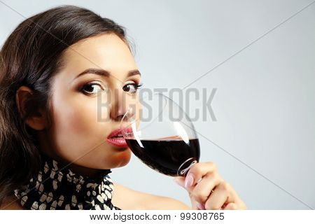 Portrait of young woman with glass of red wine on grey background