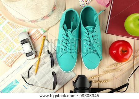 Female gumshoes with accessories on wooden background