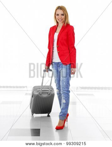 Woman holding suitcase on light background