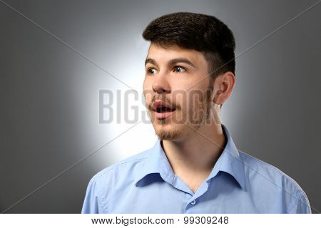 Portrait of surprised man on gray background