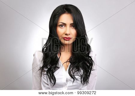 Portrait of pretty brunette on grey background