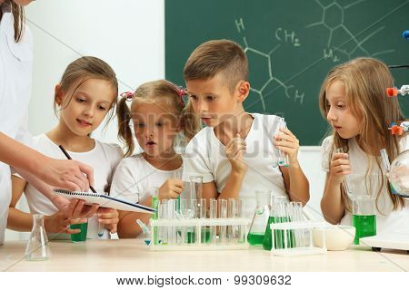 Cute pupils with teacher doing biochemistry research in chemistry class