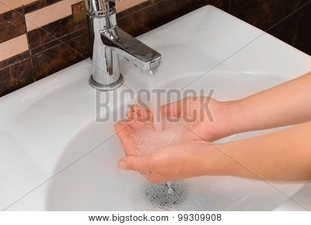 Washing hands at sink in bathroom