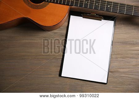 Music recording scene with classical guitar and memo pad on wooden background