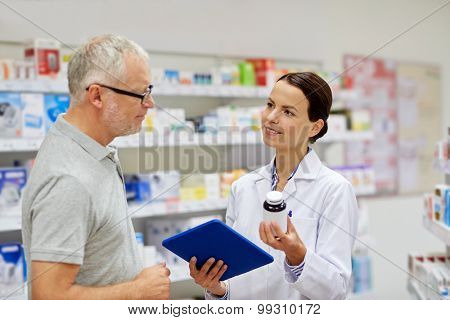medicine, pharmaceutics, health care and people concept - happy pharmacist with tablet pc computer showing drug to senior man customer at drugstore