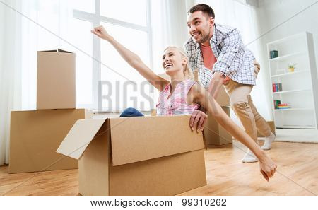 home, people, moving and real estate concept - happy couple having fun and riding in cardboard boxes at new home