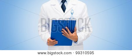 healthcare, profession, people and medicine concept - close up of male doctor in white coat with sky blue prostate cancer awareness ribbon and clipboard