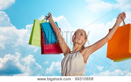 consumerism, sale and people concept - smiling woman with shopping bag rising hands over blue sky and clouds background