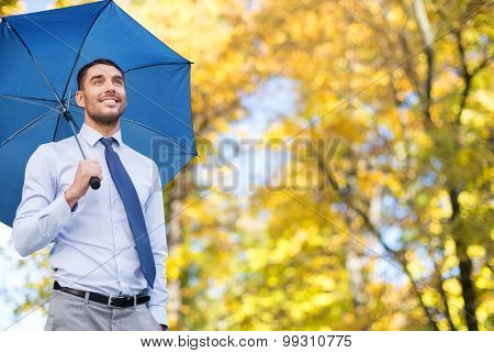 business, season, weather and people and concept - young smiling businessman with umbrella over autumn natural background