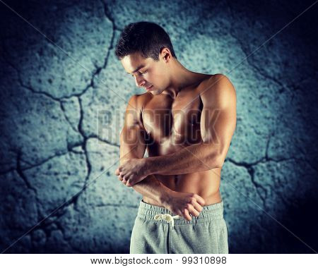 pain, sport, bodybuilding, health and people concept - young male bodybuilder touching injured elbow over concrete wall background