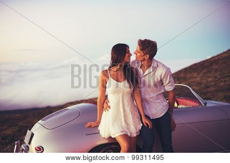 Romantic Young Attractive Couple Watching the Sunset with Classic Vintage Sports Car