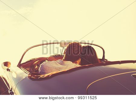 Romantic Young Attractive Couple Watching the Sunset in Classic Vintage Sports Car