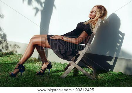 Beautiful lady in black dress sitting in the garden