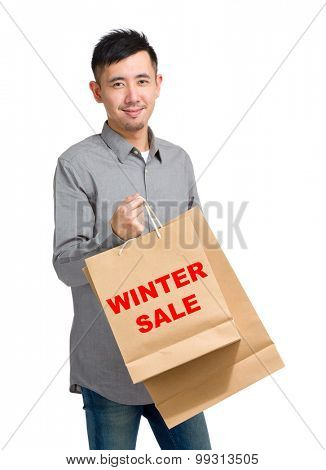 Asian man hold with shopping bag and showing winter sale