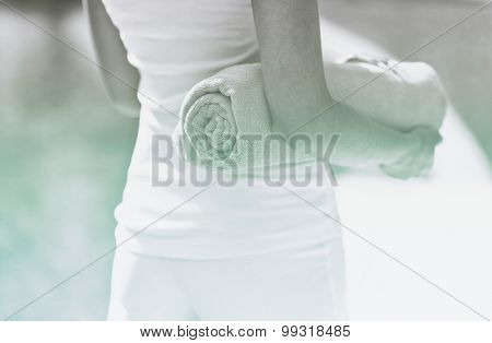 Slender Woman in White Casual Clothing Holding a Rolled Towel for an Outdoor Relaxation.