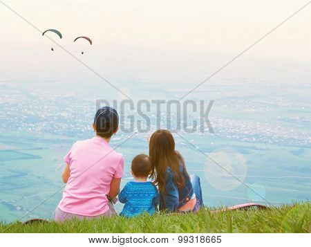 Portrait of family mother taking photo paraglider with brother and sister together sitting in nature