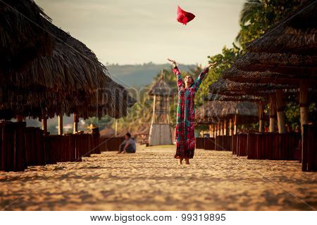 Slim Girl In Long Throws Up Big Red Hat Among Reed Umbrellas