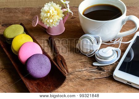 macaroons and a cup of coffee with cellphone on wooden table