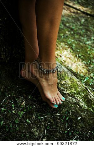 barefoot woman legs with anklet bracelets stand by tree in moss, natural light, selective focus
