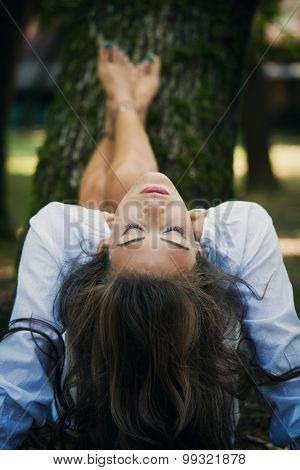 woman relax in nature, legs lean on tree, head thrown backwards, eyes closed, selective focus, natural light