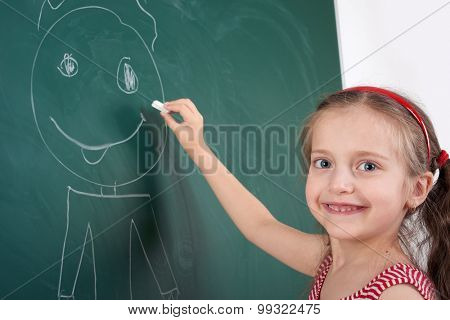 girl drawing faces on the school board