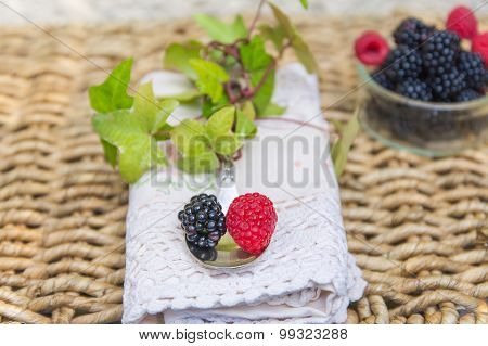 blackberries and raspberries with spoon.