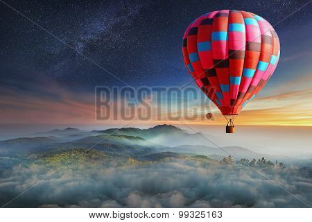 Colorful hot-air balloons flying over the mountain with with stars. Beautiful mountains landscape