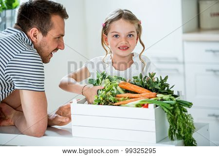 Father And Daughter With Vegetable Box In Kitchen