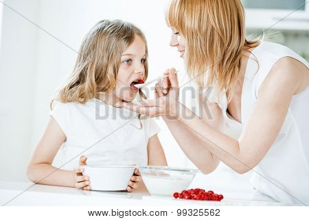 Mother Feeding Daughter With Muesli And Raspberries