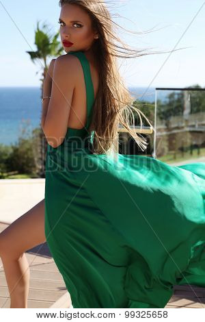 Young Woman With Long Blond Hair In Luxurious Green Silk Dress