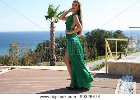 Young Woman With  Blond Hair In Luxurious Green Silk Dress