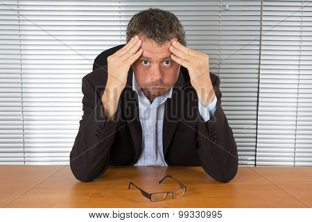 Desperate  Businessman Leaning On Both Hands Behind His Laptop