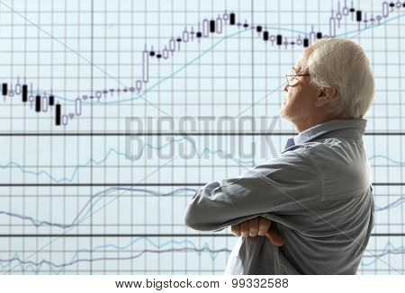 Aged stock trader looking at monitors