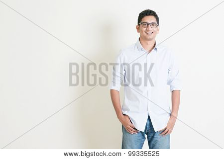 Portrait of handsome casual business Indian male smiling, hands in pocket, standing on plain background with shadow, copy space at side.